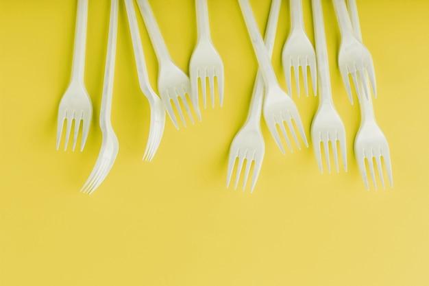 Talheres de plástico em uma superfície amarela