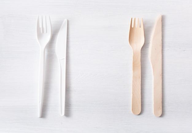 Talheres de plástico prejudiciais e talheres de madeira ecológicos. conceito livre de plástico