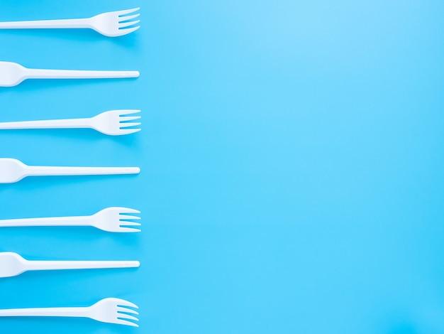 Talheres descartáveis, colheres de plástico branco, garfos, copos e pratos isolados