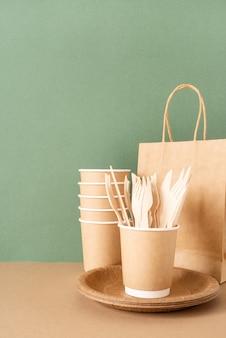 Talheres descartáveis ecológicos em saco de papel de superfície verde, copos, garfos e facas