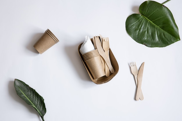 Talheres descartáveis ecológicos feitos de papel e madeira de bambu. copos, facas e garfos isolados. Foto gratuita