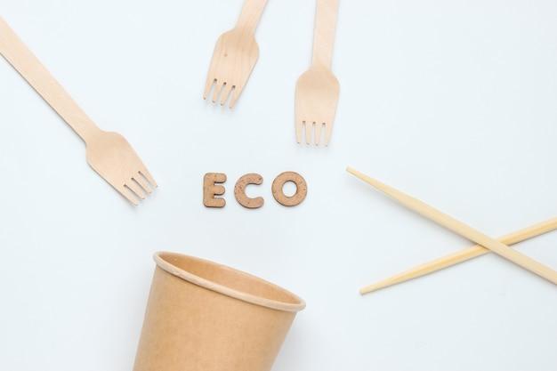 Talheres descartáveis em materiais naturais. conceito ecológico. garfos de madeira, xícara de café artesanal vazia, pauzinho em um fundo branco.