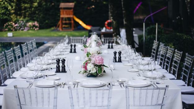 Talheres e copos com faca garfo de flores servida no jantar em restaurante com interior aconchegante