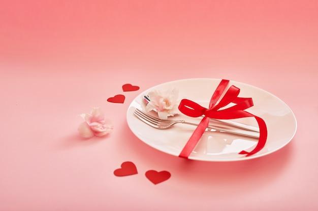 Talheres e um prato com corações em uma superfície rosa para dia dos namorados