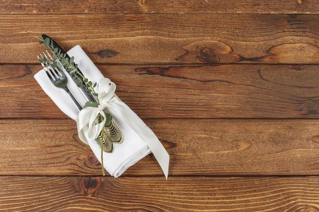 Talheres, embrulhado em um guardanapo sobre uma mesa de madeira