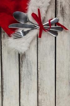 Talheres embrulhados com motivo do natal em uma mesa de madeira