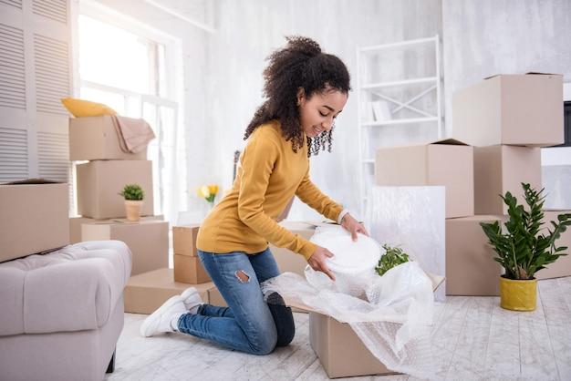 Talheres favoritos. linda garota tirando os pratos da caixa enquanto desempacota seus talheres, tendo se mudado para uma nova casa