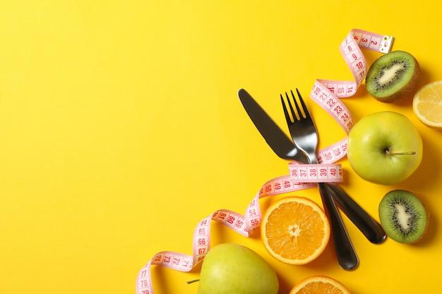 Talheres, fita métrica e frutas em fundo amarelo