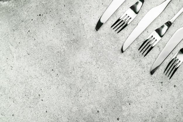 Talheres, garfos e facas em um concreto leve