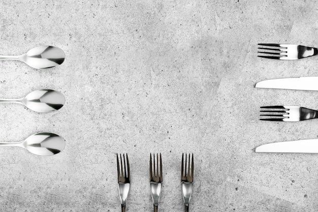 Talheres. garfos e facas na luz de fundo de quadro de concreto.