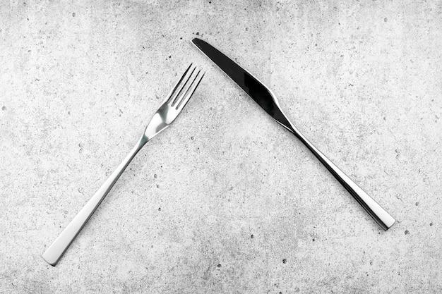 Talheres. garfos e facas, sobre um fundo claro e concreto. vista plana leiga, superior.