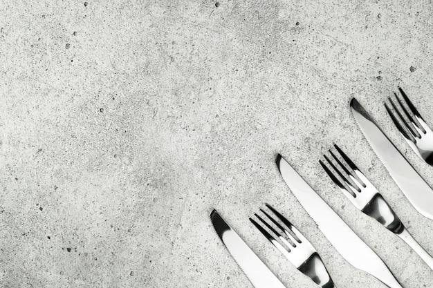 Talheres. garfos e facas, sobre um fundo claro e concreto.