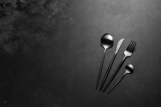 Talheres pretos sobre uma mesa escura de concreto. preparação da mesa de jantar