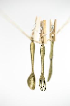 Talheres vintage decorativos pequenos pendurados em uma corda isolada no branco