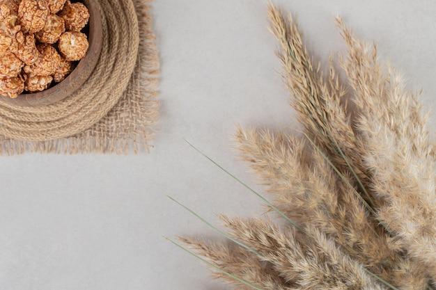 Talos de grama seca ao lado de uma tigela de madeira em um tripé, cheia de pipoca cristalizada no fundo de mármore.