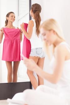 Talvez este vestido? mulher jovem e bonita segurando o vestido e olhando no espelho enquanto outra mulher está sentada em primeiro plano e olhando para o telefone celular
