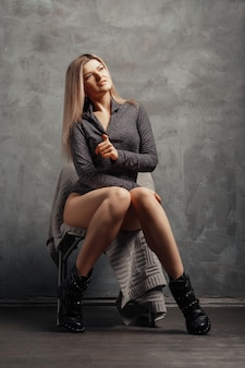 Tamanho bonito mais modelo sentado na cadeira perto da parede abstrata grunge