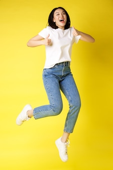 Tamanho real de feliz jovem asiática pulando de alegria, mostrando os polegares em aprovação, posando sobre fundo amarelo em jeans e camiseta branca casual.
