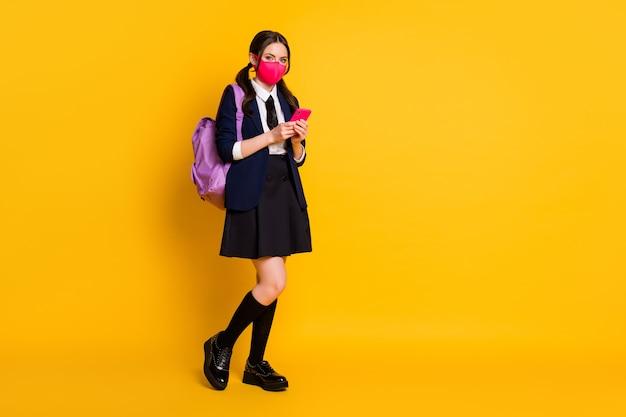 Tamanho total do corpo da garota voltando para a escola segurar telefone usar máscara uniforme escolar