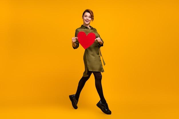 Tamanho total do corpo de uma garota alegre vai segurar um coração vermelho