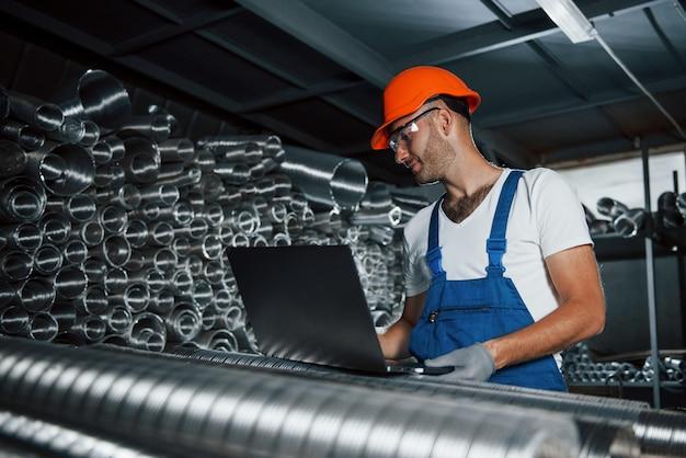 Tamanhos diferentes de tubos de ventilação. homem de uniforme trabalha na produção. tecnologia industrial moderna.