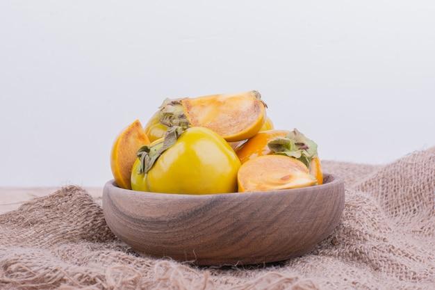 Tâmaras de ameixa amarela em copo de madeira
