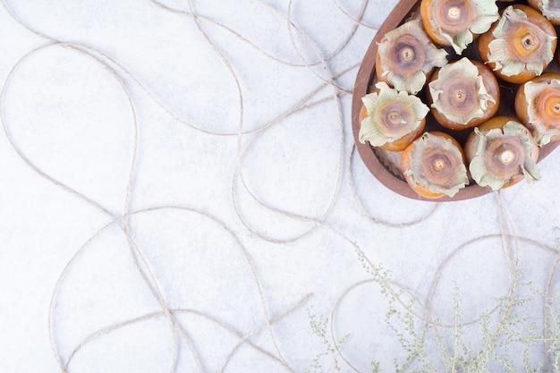 Tâmaras de ameixa em uma bandeja de madeira na superfície cinza