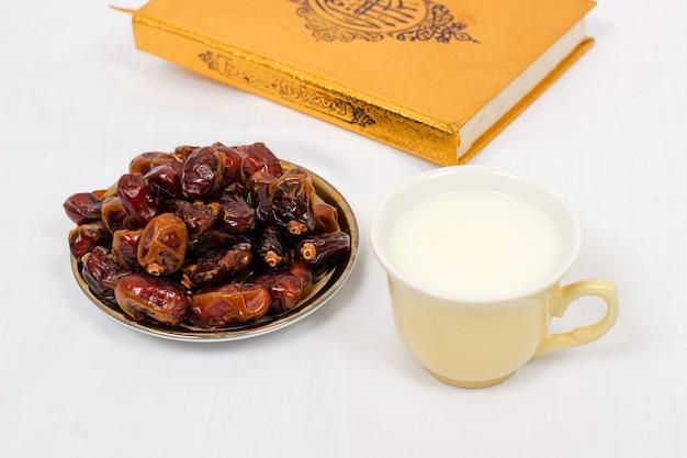 Tâmaras do alcorão e um copo de leite isolado em um fundo branco