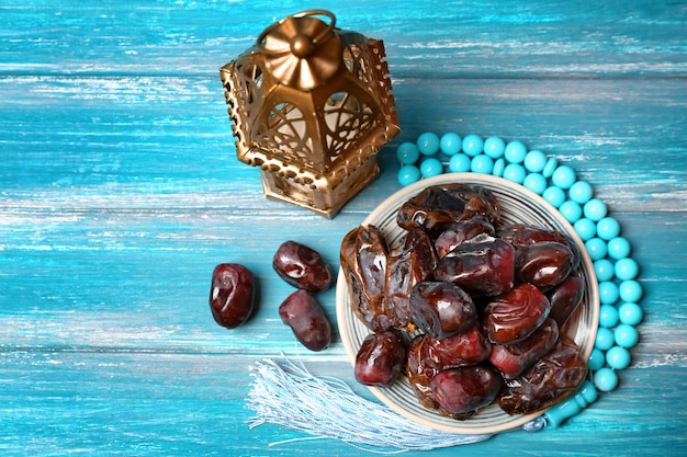 Tâmaras saborosas e lâmpada muçulmana na mesa de madeira