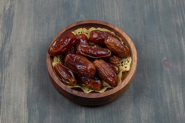 Tâmaras saborosas secas em uma tigela de madeira