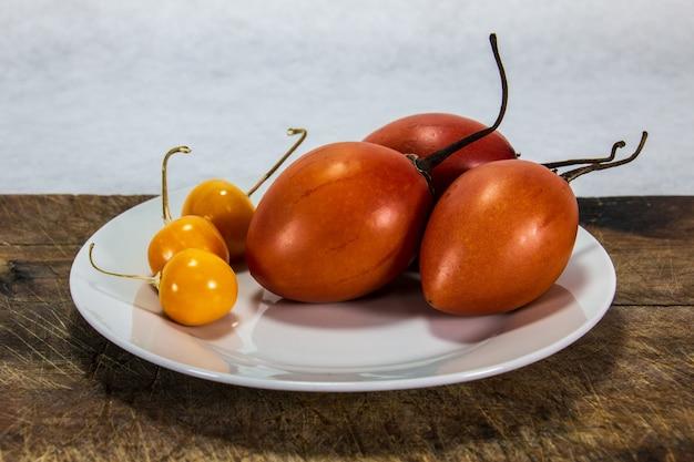 Tamarillo ou tomate árvore em uma placa de madeira ao lado de uvilla ou aguaymanto physalis