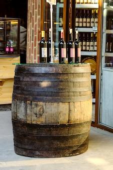 Tambor de madeira velho com vinho e garrafa do vinho sobre ele.