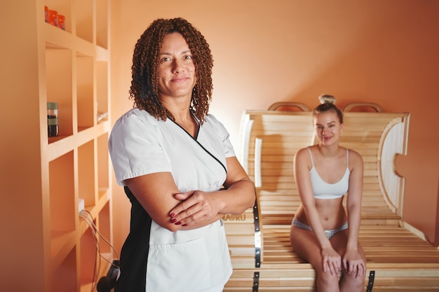Tambor phyto de madeira, sauna horizontal. linda mulher autêntica massagista e seu cliente na sala de bem-estar antes dos tratamentos de spa