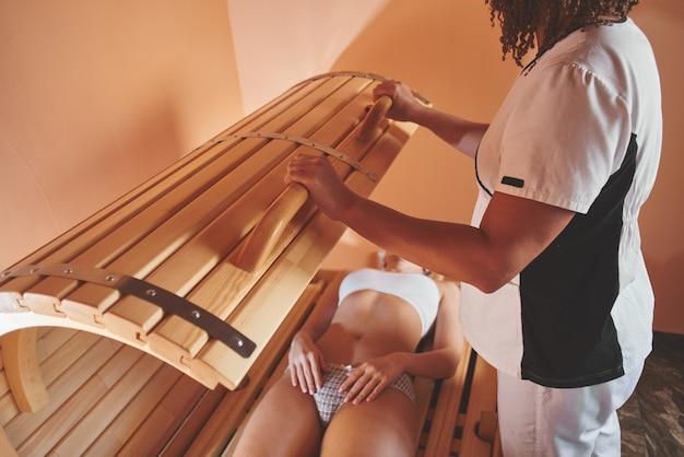 Tambor phyto de madeira, sauna horizontal. massagista de mulher bonita, aplicar tratamento de spa para uma jovem mulher em uma sala de bem-estar