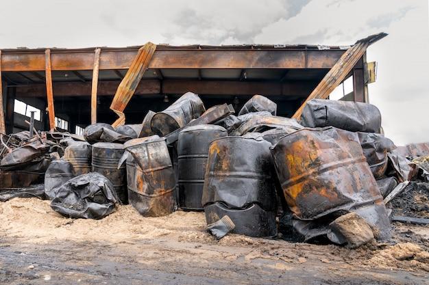 Tambores carbonizados queimados de óleo de motor no armazém queimado.