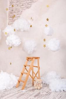 Tamborete de madeira da escadaria com as nuvens na sala de crianças.