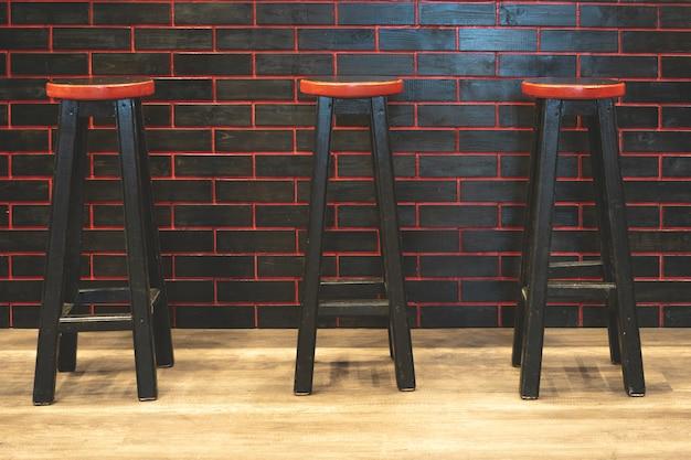 Tamboretes de barra pretos com um assento vermelho.