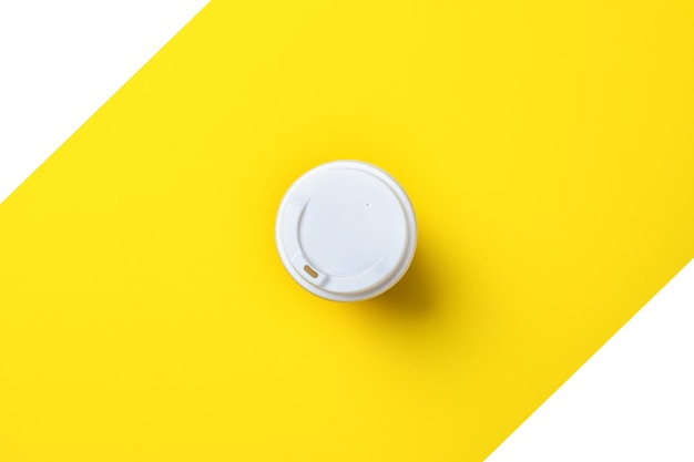 Tampa branca em um vidro de papelão de cima em um amarelo-branco.