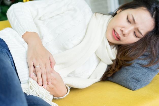 Tampa da mulher asiática para aliviar a dor no estômago depois de sentir o período menstrual