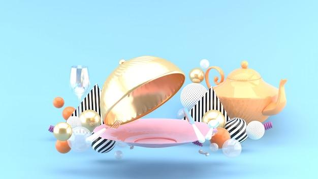 Tampa de comida dourada, prato, copo de vinho e bule rodeado por bolas coloridas em um espaço azul