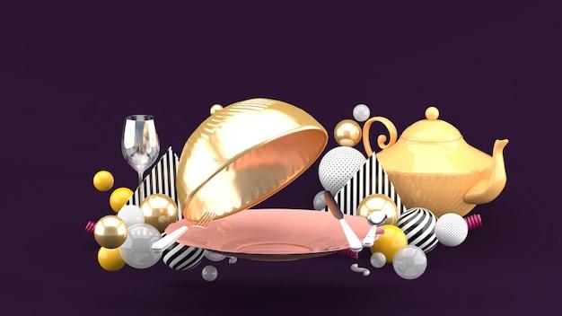 Tampa de comida dourada, prato, copo de vinho e bule rodeado por bolas coloridas em um espaço roxo