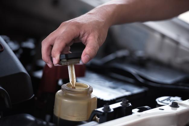 Tampa do fluido de direção hidráulica aberta, manutenção do carro.