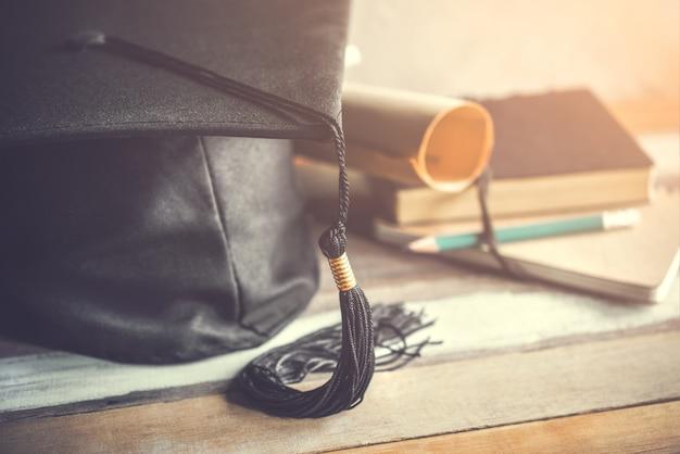 Tampão da graduação, chapéu com papel do grau no conceito de madeira da graduação da tabela.