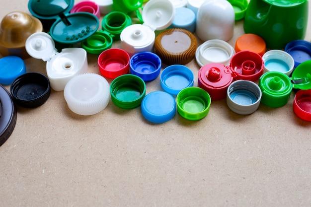 Tampas de garrafa de plástico coloridas e tampa de vidro plástico em fundo de madeira compensada. vista do topo