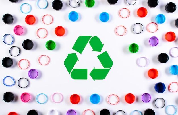 Tampas de garrafa de plástico colorido com símbolo de reciclagem. dia mundial do meio ambiente ou reutilização, conceito de reciclagem.