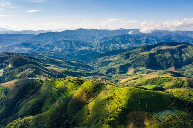 Tampas de montanha de alto ângulo e caminho de estrada com céu azul na temporada de chuva