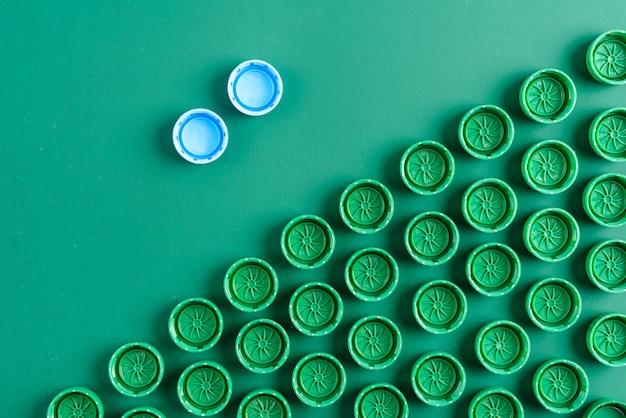 Tampas de plástico verdes para garrafas de estimação em um fundo