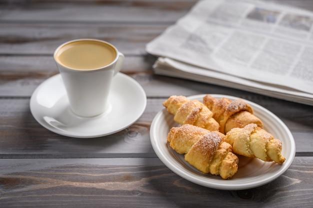 Tampinha de café e biscoitos caseiros em uma superfície de madeira perto de um jornal seletivo