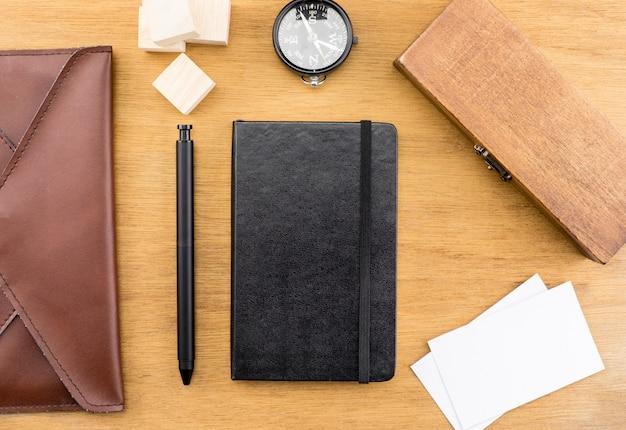 Tampo da mesa com bússola, caixa de madeira, caderno, bolsa de couro, cartão de visita e caneta