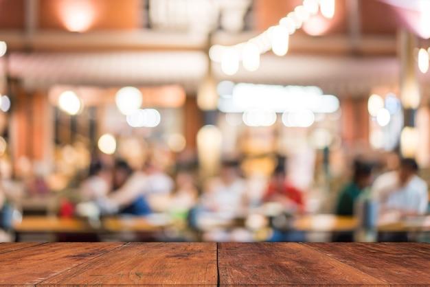Tampo da mesa de madeira com borrão de pessoas no café ou no fundo (café, restaurante)